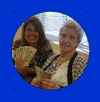 Two women showing their winnings from bingo
