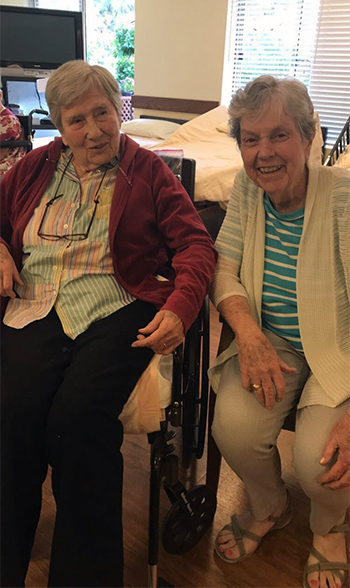 Two elderly women sitting in wheel chairs chatting with each other.