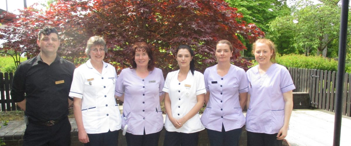 A group of 6 uniformed staff, both nurses and carers, at Nazareth House Sligo standing in front of a tree in full bloom on a decked outdoor space