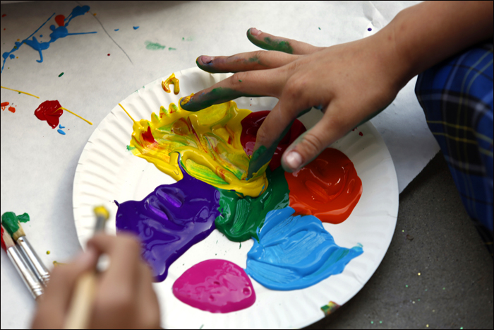 Children fingers dipping into colorful paint on a dish