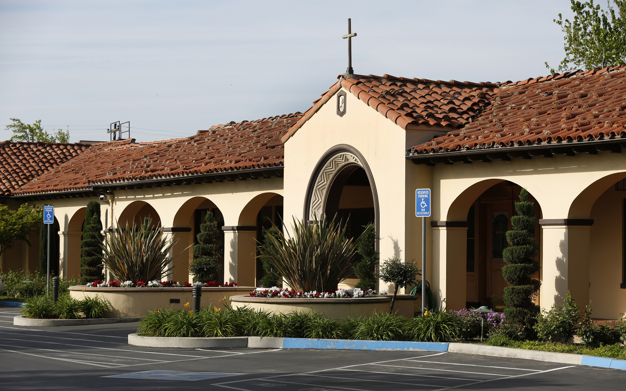 Entrance to House Fresno Assisted Living Home with Spanish architecture, tile roof, porticoes, and lush garden greenery.