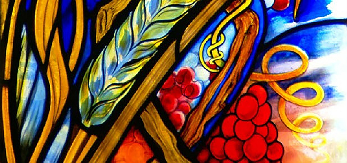 Stained glass window with Eucharistic symbols: bread wheat, graps