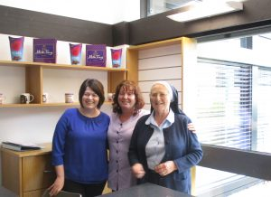 Three smiling ladies (Breda Casey, Director of Nursing, Paula O'Connor, Carer and Sr. Margaret, Mother Superior) grouped together standing behind the counter at the opening of Nazareth House shop. In the background, some of the confectionary and gift items are on display