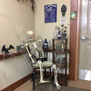 Skeleton sitting in a chair surround by old fashioned chemical compounds